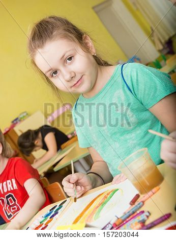 funny girl draws paints and pencils brightest pictures in kindergarten - Russia Moscow - February 04 2016