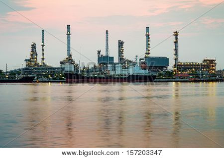 Oil refinery river front with reflection during sunrise