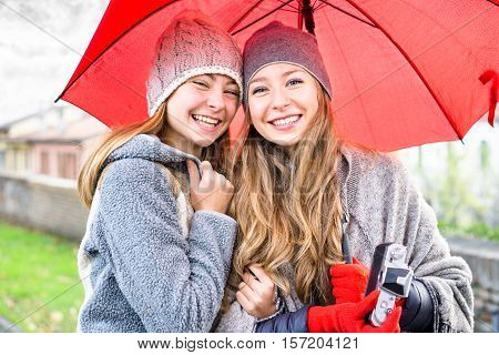 Young women holding red umbrella smiling at camera in winter clothing and headgear - Best cute girlfriends laughing outdoors hugging each other in a cold cloudy day - Autumn concept of travel and joy