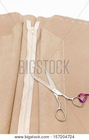 Cloth, scissors and zipper. Dressmaker prepares wrap detail with sketch lines.