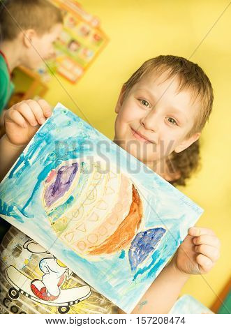Cheerful Smiling Boy Holding A Bright Colorful Picture Painted Colors And Crayons In Kindergarten -