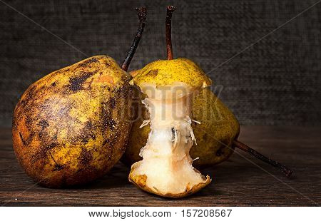 Two pears and stub standing on wooden table background sacking