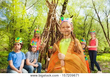 Portrait of happy girl in handmade headdress playing Injuns with her friends in the summer forest poster