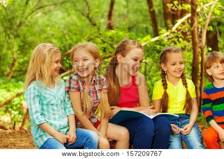 Portrait of five cute kids reading fairy-tales sitting in the summer camp in the forest