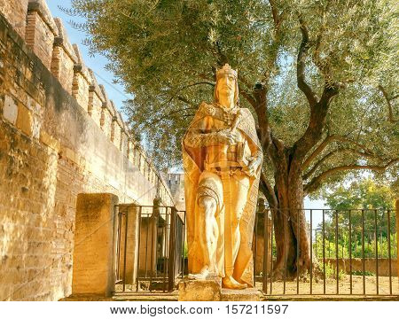 The sculpture of King Alfonso XI wise at the entrance to the Alcazar. Cordoba. Andalusia.