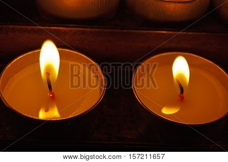 Two votive candles (tea light) in a church on a dark background
