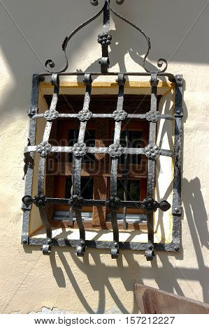 Detail of a window with an iron grate. Engadine Switzerland Europe