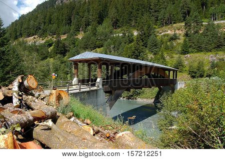 Wooden bridge with a roof on the river Inn in Engadine Switzerland Europe