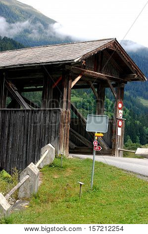 Detail a wooden bridge with a roof on the river Inn. Engadine Switzerland Europe