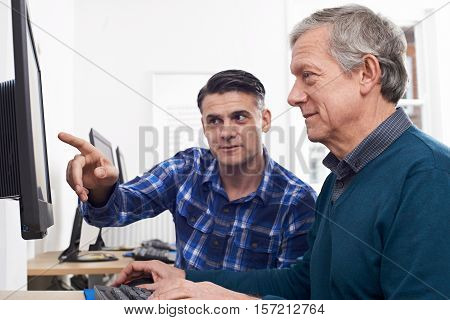 Tutor Helping Mature Man In Computer Class