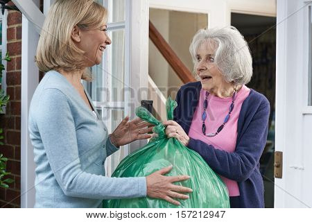 Woman Taking Out Trash For Elderly Neighbour