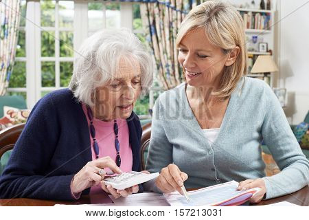 Female Neighbor Helping Senior Woman With Domestic Finances