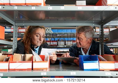 Male Engineer With Female Apprentice Checking Stock Levels
