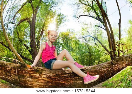 Close-up portrait of cute young girl sitting on a tree trunk in the forest at sunny day