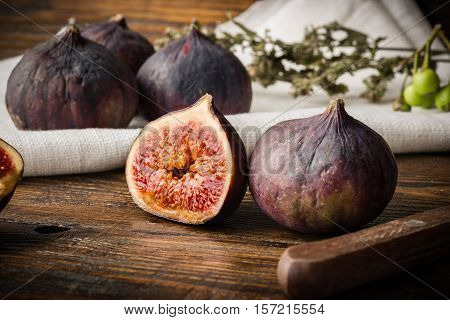 Ripe purple figs on wooden table with sliced one fig and other things