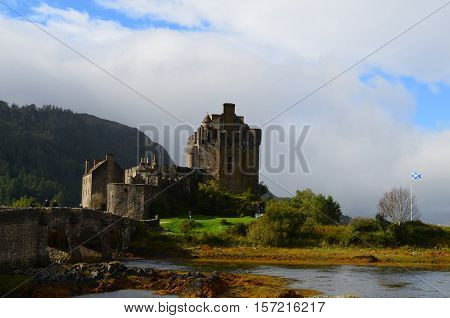 Scottish flag and landscape at Eilean Donan Castle.