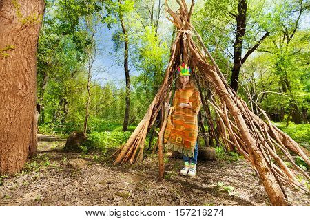Portrait of cute girl in Indian costume standing at the tepee in the forest