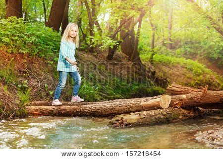 Portrait of little blond girl crossing log bridge in the forest at sunny day