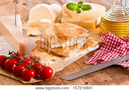 Cheese focaccia bread and other ingredients on baking paper.