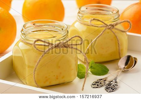 Orange curd (english citrus cream) in glass jars .