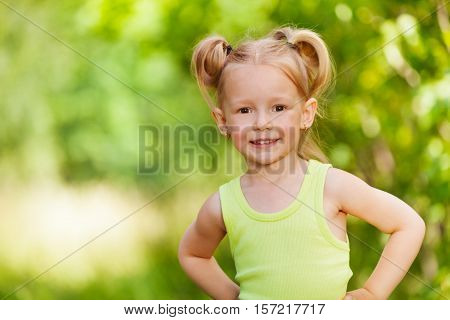 Close-up portrait of smiling three years old girl standing and looking at camera