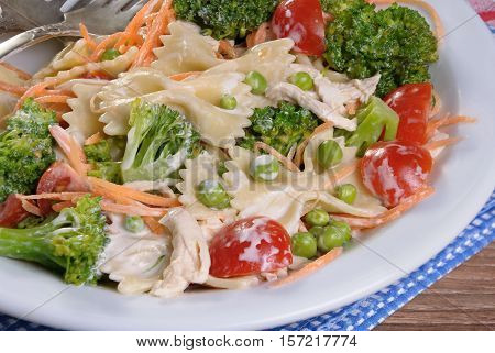 pasta salad with chicken tomatoes broccoli green peas carrots dressed with sour cream