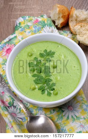 A plate of soup puree of green peas with parsley on a table