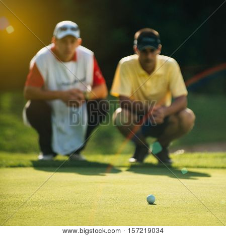 Golfer And Caddy Reading Green