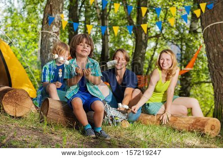 Happy little boy cooking marshmallows with his family at campsite in summer