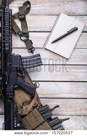 Notebook pen assault rifle and battle belt with rifle ammo in magazine on wooden table.Top view