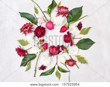 Round frame of flowers. Decorations of red roses buds green leaves and white chrysanthemums on gray concrete background. View from above flat