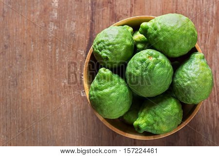 Close up fresh bergamot in wooden bowl on dark wood table background. bergamot on old wooden brown with copy space. (Bergamot or Kaffir lime)