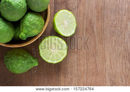 Close up fresh bergamot and bergamot slice in wooden bowls on dark wood table background. bergamot on old wooden brown with copy space. (Bergamot or Kaffir lime)