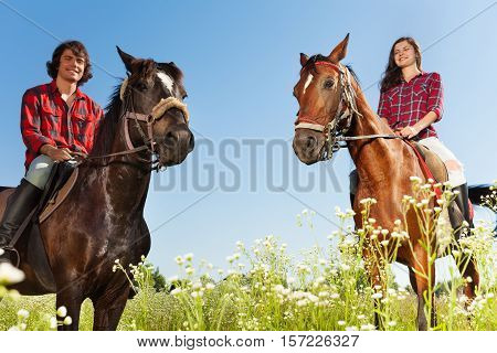 Portrait of young people horseback riding in flowery meadows at sunny day
