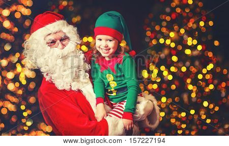 happy cheerful laughing child elf helper in the hands of Santa Claus at Christmas
