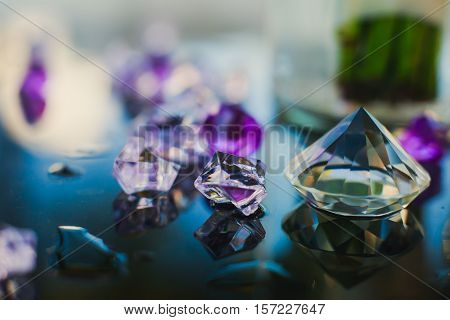 Diamond small purple jewel stones heap over mirror glass table, crystal stones, shiny gold and silver jewelery on a table