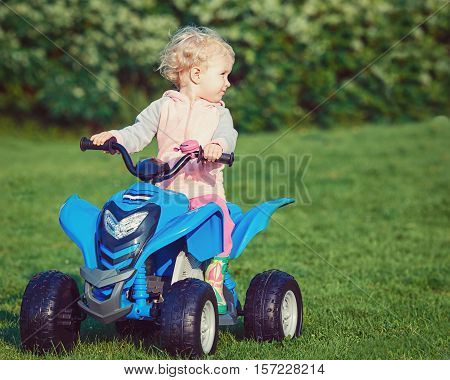 Portrait of cute adorable happy little blond Caucasian boy girl child driving blue electric car in park outside on sunny windy summer day