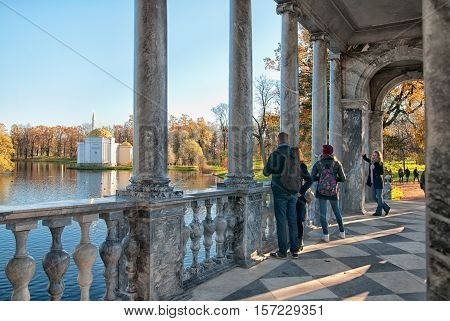 TSARSKOYE SELO, SAINT - PETERSBURG, RUSSIA - OCTOBER 19, 2016: People on The Marble Bridge near the Great Pond in the Catherine Park. On the background is The Turkish Bathhouse Pavilion.