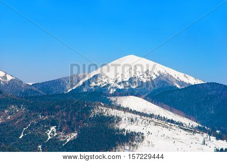 Snowy peak of Mount Hoverla at 2061 metres (6762 ft) - the highest mountain in Ukraine and part of the Carpathian Mountains a notable tourist attraction extreme sports site in the winter period.