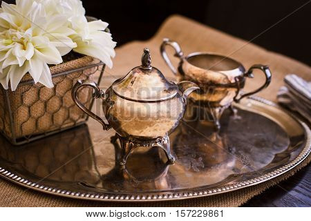 An Antique teapot and on a sliver platter on a table