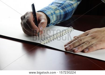 student in casual wear makes notes in a notebook on the academic lecture