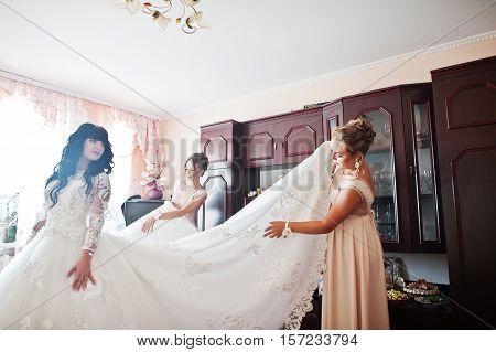 Bridesmaids Preparing Wedding Dress Of Bride On Morning Wedding Day.