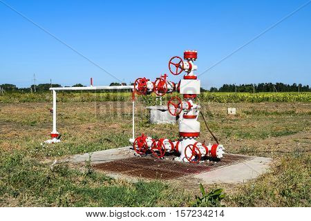 Oil Well In The Field, Painted In White And Red. Oil With Modern Equipment.