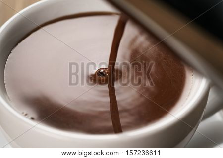 hot chocolate pouring in cup, shallow focus