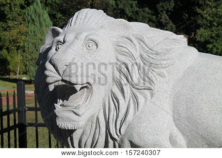 White stone lion roaring in the park