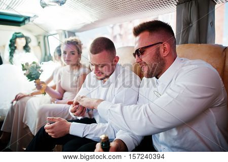 Stylish Groomsman Or Best Man Of Groom And Bridesmaids Inside Limousine At Wedding Party.