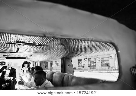Stylish groomsman or bes man of groom and bridesmaids with wedding couple inside limousine at wedding party drinking champagne. Black and white photo