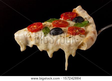 A hot pizza slice with dripping melted cheese. Isolated on black.