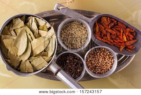 Spices in metal containers. Bay leaves, cummin, pepper and cloves.