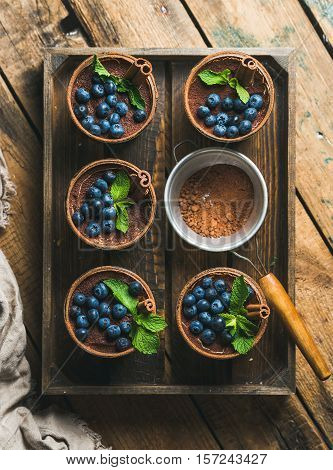 Homemade Tiramisu dessert in glasses with cinnamon sticks, mint leaves, fresh blueberries and sieve with cocoa powder in wooden tray over rustic wooden background, top view, vertical composition